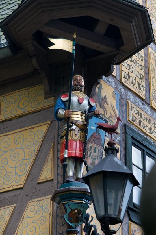 Hölzerne Ritterfigur an der Fassade, auf der Laterne die namenspendende »Rothe Amsel«